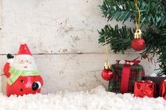 Weihnachtsmann auf dem Schnee mit Weihnachtsbaum im Weinlesehintergrund Lizenzfreies Stockfoto