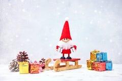 Weihnachtsmann auf einem Schlitten Sankt-Gnomhintergrund mit Geschenken und Schnee Lizenzfreie Stockfotografie