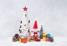 Weihnachtsmann auf einem Schlitten Sankt-Gnomhintergrund mit Geschenken und Schnee Stockfoto