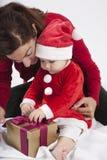 Weihnachtsmann-Baby mit der Mutter, die goldenes Geschenk öffnet Lizenzfreie Stockfotos