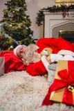 Weihnachtsmann, der auf Achselzucken mit Teddybären schläft Lizenzfreies Stockfoto