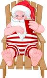 Weihnachtsmann, der auf dem Strand sich entspannt Stockbild