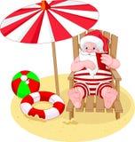 Weihnachtsmann, der auf dem Strand sich entspannt Lizenzfreie Stockbilder