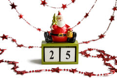 Weihnachtsmann, der auf den Würfeln zeigen das Datum 25 von Dezember auf weißem Hintergrund mit roter Girlande sitzt Lizenzfreies Stockfoto