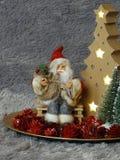 Weihnachtsmann, der auf einer Bank umgeben durch Bäume und pineappels sitzt stockbild