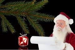 Weihnachtsmann, der Checkliste während der Weihnachtszeit vorbereitet Stockbilder