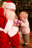 Weihnachtsmann, der dem Jungen Geschenk gibt Stockfotos