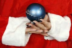 Weihnachtsmann, der eine blaue Kugel versteckt Lizenzfreies Stockfoto