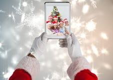 Weihnachtsmann, der eine digitale Tablette mit Foto der Weihnachtsfamilie hält lizenzfreies stockfoto