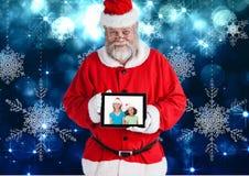 Weihnachtsmann, der eine digitale Tablette mit Foto von Weihnachten hält, scherzt Lizenzfreie Stockbilder