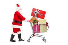 Weihnachtsmann, der einen Einkaufswagen drückt Stockfotografie