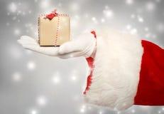 Weihnachtsmann, der einen kleinen Weihnachtspräsentkarton gibt lizenzfreie stockfotos