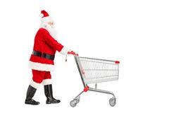 Weihnachtsmann, der einen leeren Einkaufswagen drückt Stockfoto