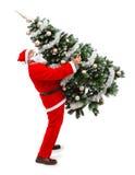 Weihnachtsmann, der einen verzierten Weihnachtsbaum trägt Stockfotos
