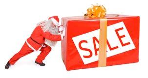 Weihnachtsmann, der großes Paket drückt Stockbild