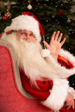 Weihnachtsmann, der im Lehnsessel sitzt Lizenzfreie Stockbilder