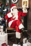 Weihnachtsmann, der mit intelligentem Telefon spricht Stockbilder