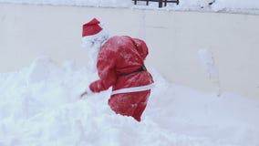 Weihnachtsmann, der mit Schaufelschnee weg nimmt, um die Weise frei zu machen stock video