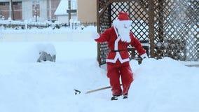 Weihnachtsmann, der mit Schaufelschnee weg nimmt, um die Weise frei zu machen und unten zu fallen stock video