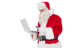 Weihnachtsmann, der online mit Laptop kauft lizenzfreies stockfoto