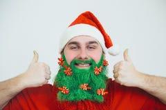 Weihnachtsmann in der roten Kleidung mit grünem Bart lächelt stockbilder