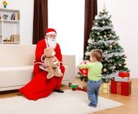 Weihnachtsmann, der Spielzeug vom Beutel zeigt lizenzfreies stockfoto