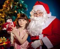 Weihnachtsmann, der Tasche anhalten und kleines Mädchen, das Spielzeug anhält stockfotos
