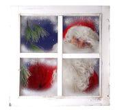 Weihnachtsmann, der von hinten ein Fenster schaut Lizenzfreie Stockfotografie