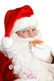 Weihnachtsmann, der Weihnachtsplätzchen isst Lizenzfreie Stockfotografie