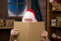Weihnachtsmann in der Werkstatt mit großem Buch Lizenzfreies Stockfoto