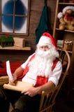 Weihnachtsmann in der Werkstatt mit Liste Lizenzfreie Stockbilder