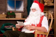 Weihnachtsmann in der Werkstatt mit Zeichen stockfoto