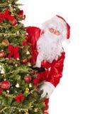 Weihnachtsmann durch Weihnachtsbaum. Lizenzfreie Stockbilder
