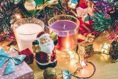 Weihnachtsmann-Griffglocken-, weiße und violetteweihnachtskerze, Verzierung verzieren frohe Weihnachten und guten Rutsch ins Neue Stockfoto