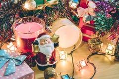 Weihnachtsmann-Griffglocken-, weiße und violetteweihnachtskerze, Verzierung verzieren frohe Weihnachten und guten Rutsch ins Neue Lizenzfreies Stockfoto