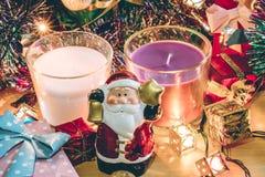 Weihnachtsmann-Griffglocken-, weiße und violetteweihnachtskerze, Verzierung verzieren frohe Weihnachten und guten Rutsch ins Neue Lizenzfreie Stockfotografie