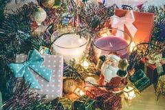 Weihnachtsmann-Griffglocken-, weiße und violetteweihnachtskerze, Verzierung verzieren frohe Weihnachten und guten Rutsch ins Neue Lizenzfreie Stockfotos