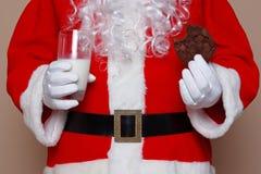 Weihnachtsmann-Holdingmilch und -plätzchen lizenzfreie stockfotos