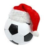 Weihnachtsmann-Hut auf der Fußballkugel Stockfotografie