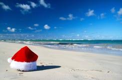 Weihnachtsmann-Hut auf karibischem Strand Stockfotografie