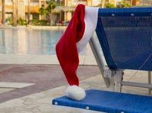 Weihnachtsmann-Hut, der an sunbed nahe dem Pool hängt Stockfotos