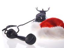 Weihnachtsmann-Hut und altes Telefon Stockbild