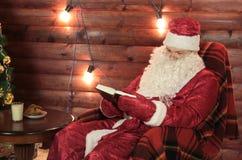 Weihnachtsmann liest ein Buch stockfoto