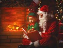 Weihnachtsmann liest ein Buch zu einer kleinen Elfe durch Weihnachtsbaum Lizenzfreies Stockfoto
