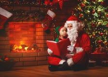 Weihnachtsmann liest ein Buch zu einer kleinen Elfe durch Weihnachtsbaum Stockfotos