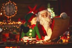 Weihnachtsmann liest Liste von guten Kindern zur kleinen Elfe durch Christm Stockbild