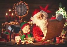 Weihnachtsmann liest Liste von guten Kindern zur kleinen Elfe durch Christm Lizenzfreies Stockbild