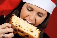 Weihnachtsmann-Mädchen, das Panettone isst Lizenzfreies Stockfoto