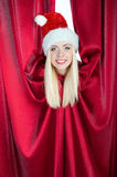 Weihnachtsmann-Mädchenblicke heraus vom Trennvorhang Stockfotografie