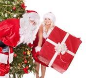 Weihnachtsmann, Mädcheneinfluß-Geschenkkasten durch Weihnachtsbaum Stockbild
